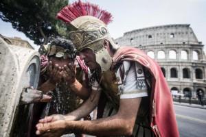 Due centurioni si rinfrescano ad una fontanella davanti il Colosseo per l'ondata di caldo nord africano sulla Capitale, Roma, 3 luglio 2015. ANSA/ANGELO CARCONI